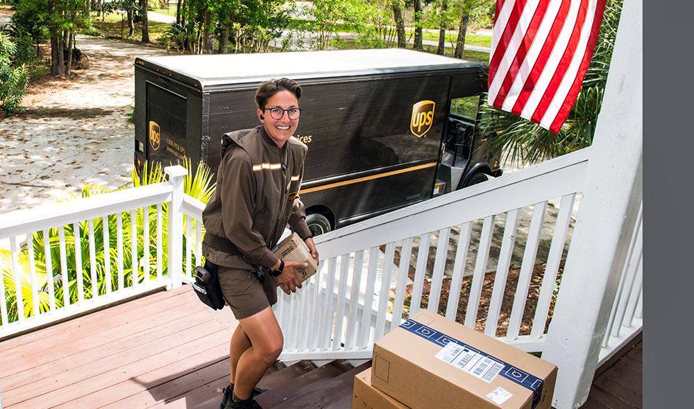 A UPS driver delivers packages to a customer's porch