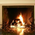 A gas log fireplace burns, warming the family room.