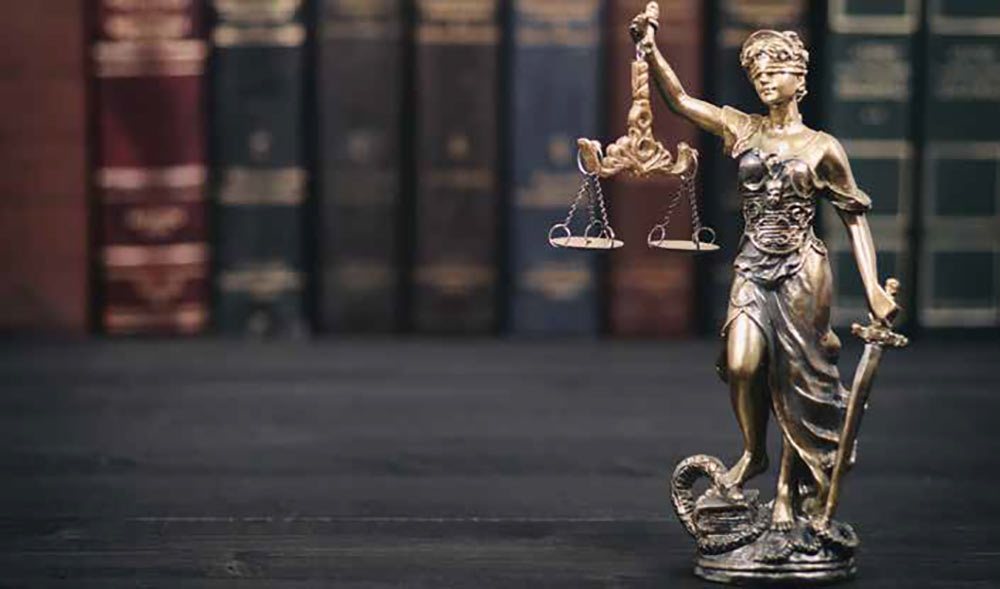 Photo of a statuette of blind justice with law books in the background. For the Buxton & Collie article.