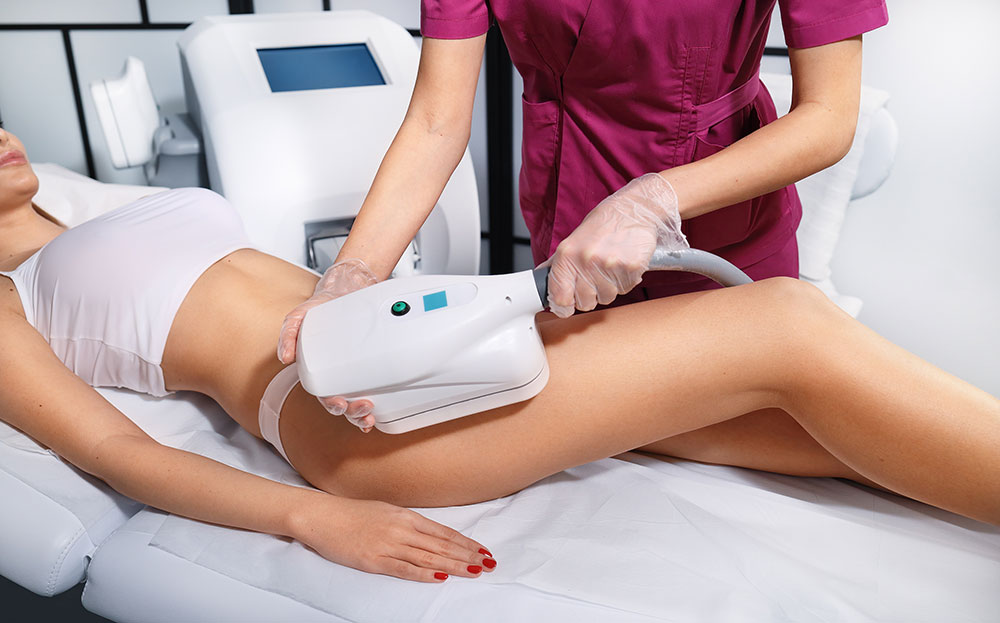 A woman receives a CoolSculpting treatment