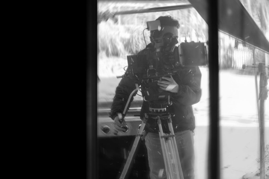 William Jacobs operating a camera with fake snow whirling about.