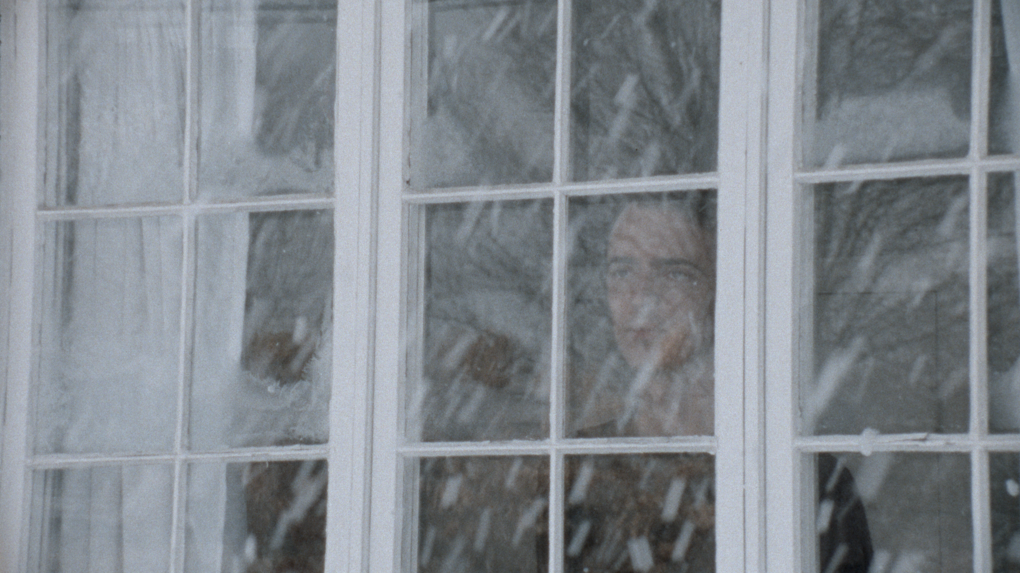 A Moment Is Enough scene still of protagonist looking at snow through window.