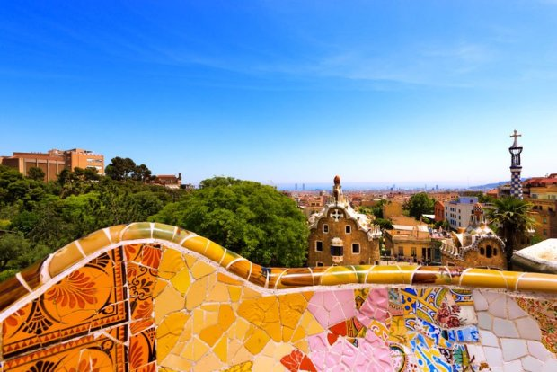 33433602 - barcelona, spain - jun 10, 2014: ceramic bench and buildings in the park guell designed by the famous architect antoni gaudi (1852-1926). unesco, world heritage site