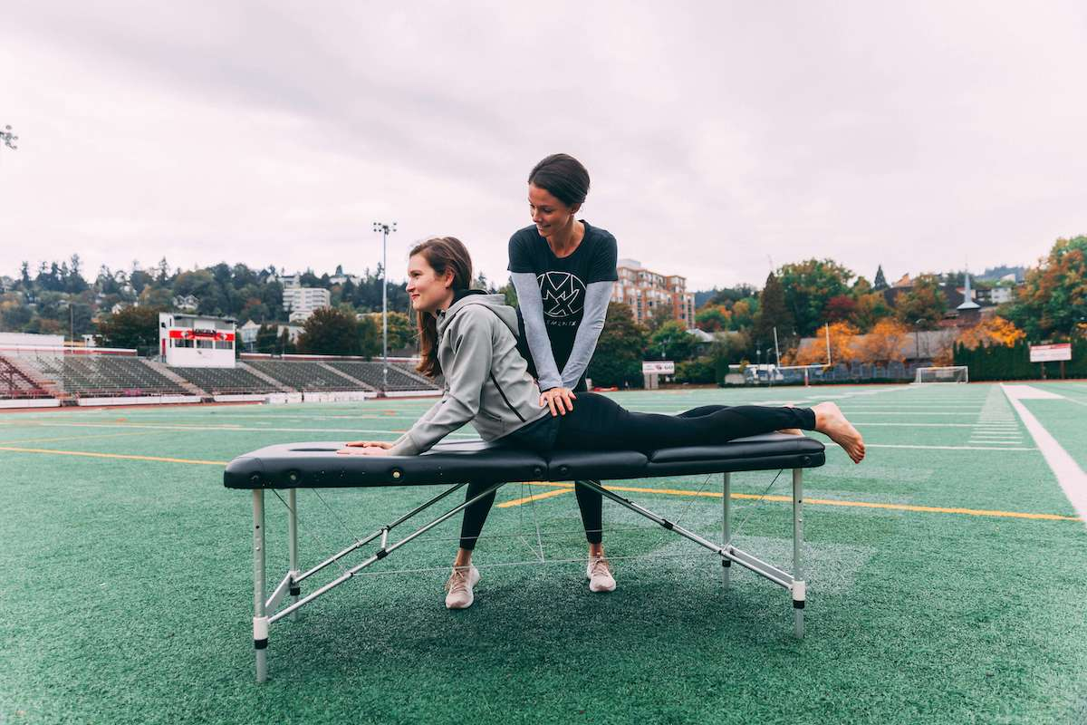 Physical therapist treating woman with low back pain on track and field in Portland, Oregon.