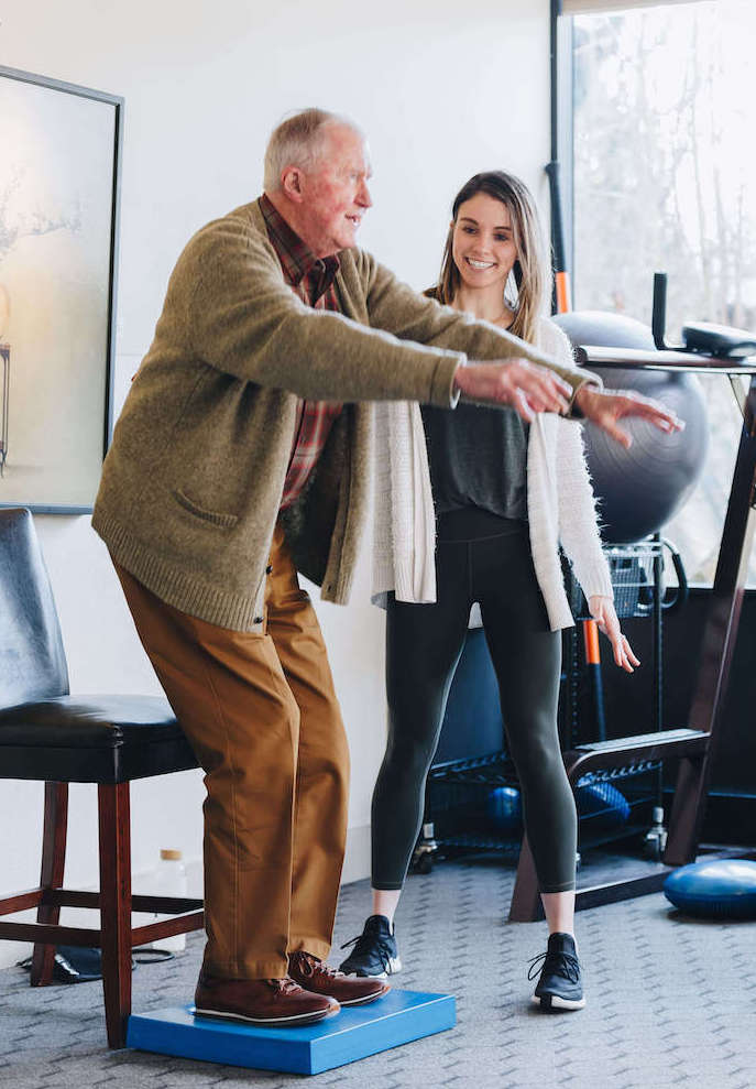Physical therapist working with an older man on balance and falls prevention