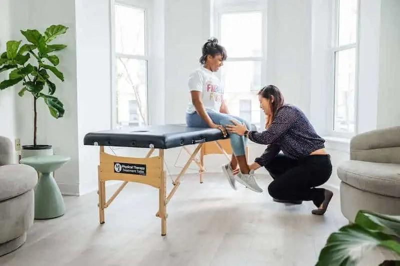 Female physical therapist treating knee pain in Arlington, Virginia