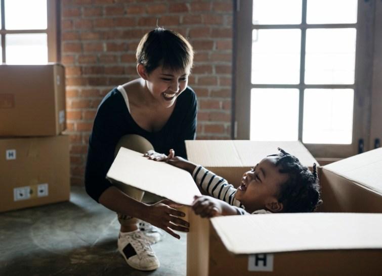 Mutter mit Kind in Umzugskarton während Umzug