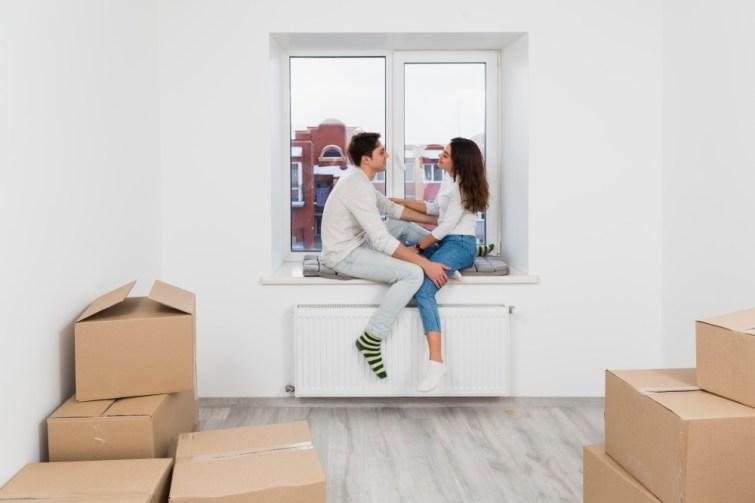 Einweihungsgeschenk Paar: Pärchen sitzt im Zimmer nach dem Umzug