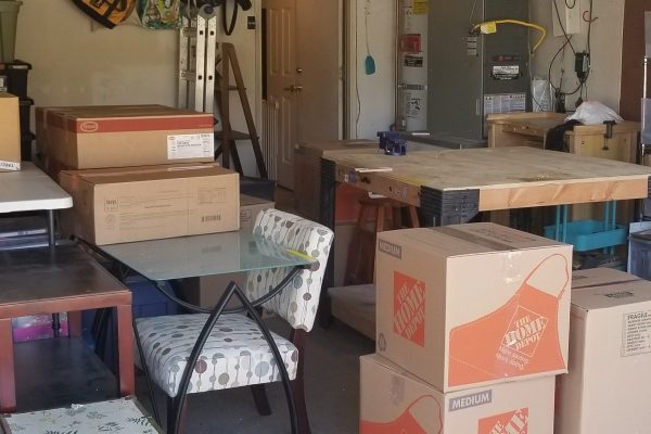 Picture of how Movers and Movers taking out boxes, tables, night stands and dressers from the garage to the truck
