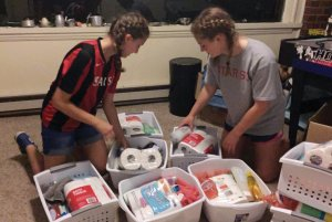 Students Reilly Curp and Mia Huber sort items collected for local refugee families.