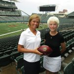 Katie Blackburn and Nancy Brown, Toy Shop auxiliary members, with a Marvin Lewis-autographed football from the Bengals Auction Table