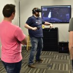 Jevan Fleenor, project coordinator, dances it up in virtual reality while Oodle partner, Ryan Hughes, waits his turn.