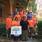 A homeowner with the crew that helped landscape and paint her home