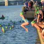 Amy Brossart joins swimmers in green caps, signifying they are not racing