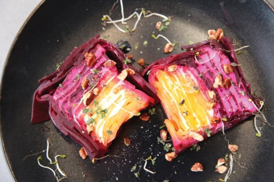 Beet and goat cheese terrine with smoked walnuts, burnt honey and broccoli sprouts