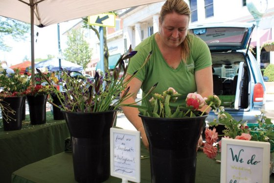 Hyde Park Farmers' Market - Hazelfield Farm in Worthville, Kentucky, produces almost five acres of specialty cut flowers and over twice that much in fresh vegetables, fruits, herbs and grains. Owners Raphe and Teresa started selling at Hyde Park Farmers' Market during its first season, 14 years ago. Their daughter, Sayward (pictured), tends the floral stand, arranging bouquets to order.