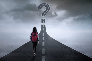 Student walking on the highway while looking at a question mark