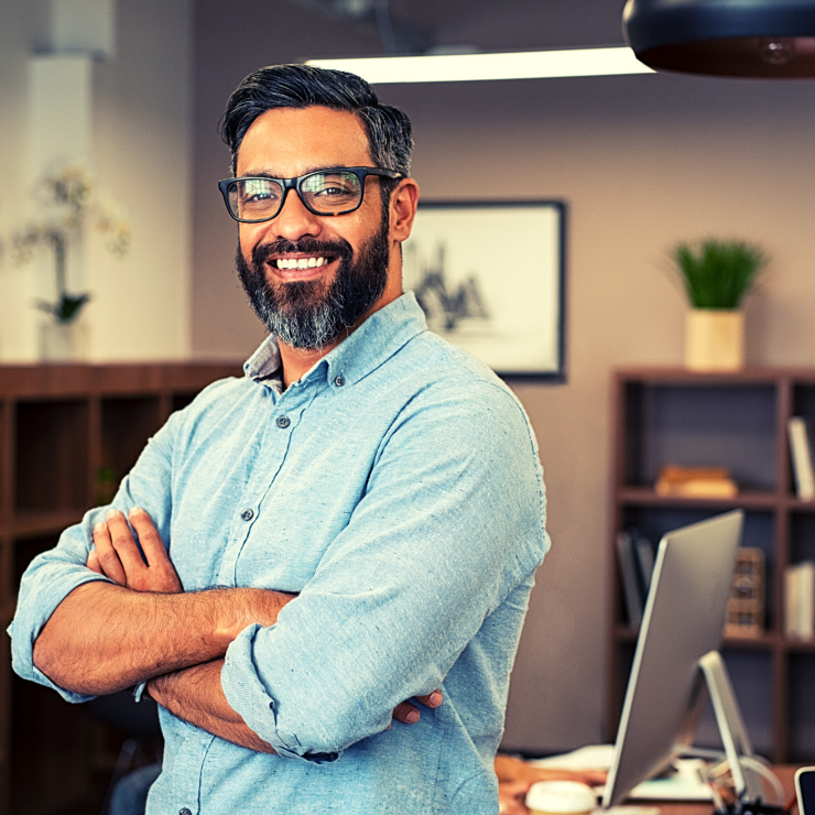 man standing in office folding arms while smiling