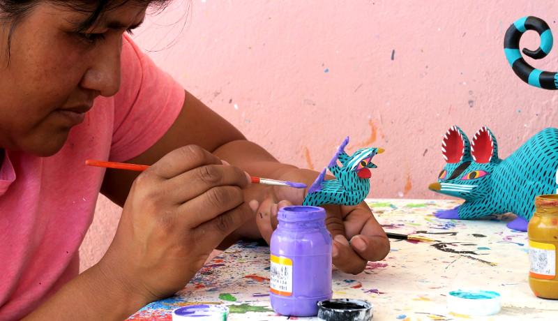 Antonia, die Frau von Armando Jimenez, beim Bemalen einer Maus im traditionellen Design