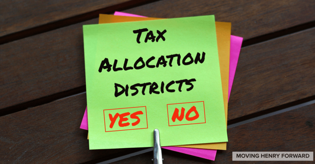 """Photo of sticky note with text """"Tax Allocation Districts YES NO"""" (staff photo)"""
