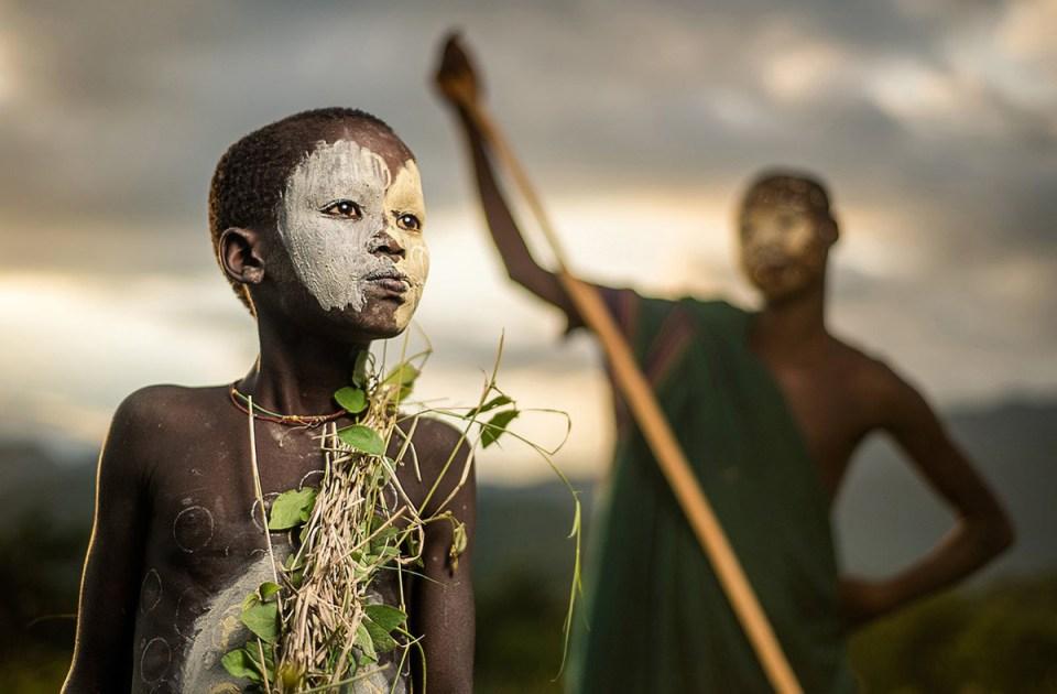 Un garçon de la tribue nomade Suri en Ethiopie portant la peinture faciale et corporelle traditionnelle.