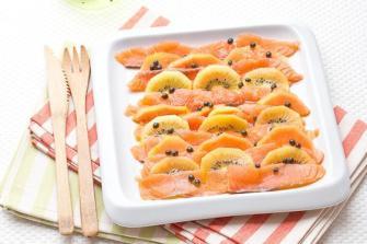 Un carpaccio de saumon avec de la papaye et des kiwis