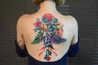 Des tatouages délicats inspirés par la nature ornent la peau de couleurs vives