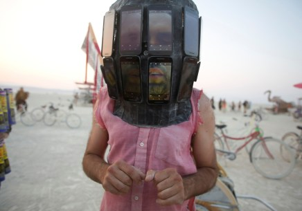 Derek Schoonmaker walks on the playa with his helmet made of android phones during the annual Burning Man festival in the Black Rock Desert of Nevada