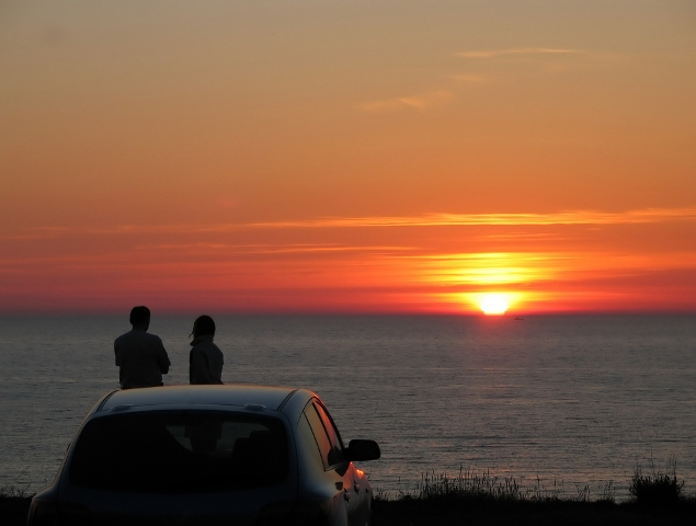 man and woman are watching a sunset