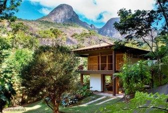 Une maison à étage en bois entre rivière et montagne au Brésil