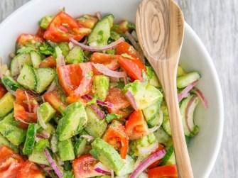 Une salade composée de concombres, de tomates et d'avocats