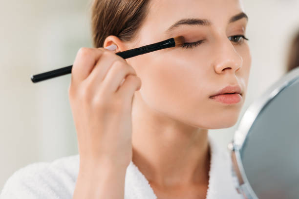 close-up view of beautiful young woman applying eyeshadow with brush