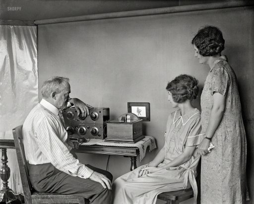 "1925. ""Motion pictures by radio are very near, predicts C. Francis Jenkins, who has designed this small radio-vision receiving set for use in the home. It is only a few inches square and is attached to the regular radio receiving set. A miniature motion picture screen is placed on the wall of your home, as shown in this photo. The first of this machine to be made. The photo was taken in Mr. Jenkins's laboratory at Washington, D.C."" Harris & Ewing glass negative."