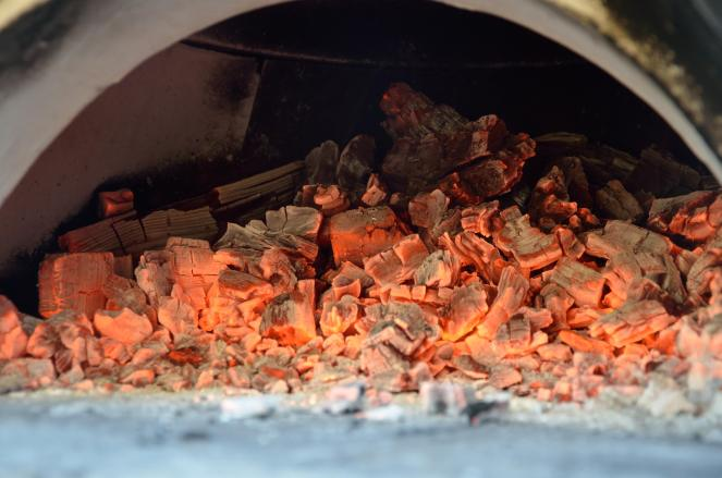 The red hot coals continue to heat the oven ... you can see the black soot begin to cook off of the side of the oven, leaving the white, hot brick.