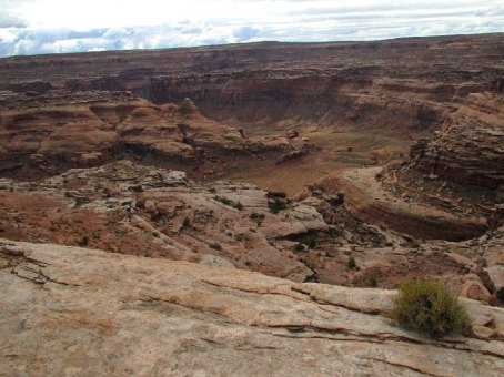 """View from Horseshoe Canyon: Horseshoe Canyon meets the Green River near the top of a horseshoe shaped abandoned meander of the river; hence the name Horseshoe Canyon. Horseshoe Canyon comes in at the far side of the photo. The now isolated island of rock the river used to wind around was called by the old cowboys """"The Frog."""" From the Park's Facebook page."""