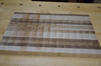 When it was cut into strips to make it an end-grain cutting board, one piece of hard maple was revealed to have spalting in the middle of the board ... the little dots in the middle of the board. The grain pattern was no longer symetrical, so I moved 4 strips from one end to the other in order to center the unique grain pattern in the hard maple.