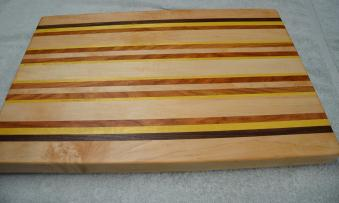 "# 62 Cutting Board, $150. Hard Maple, Walnut, Yellowheart and Cherry. 22-1/8"" x 14-3/8"" x 1-5/8"". Edge grain."