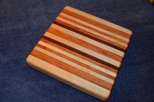 "# 23 Cutting Board, $50. Edge grain. 12"" x 12"" x 1-1/2"". Maple, cherry and walnut."