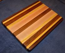 "Cutting Board # 15 - 008. Black Walnut, Yellowheart, African Teak and Hard Maple. 12"" x 16"" x 1-1/4""."