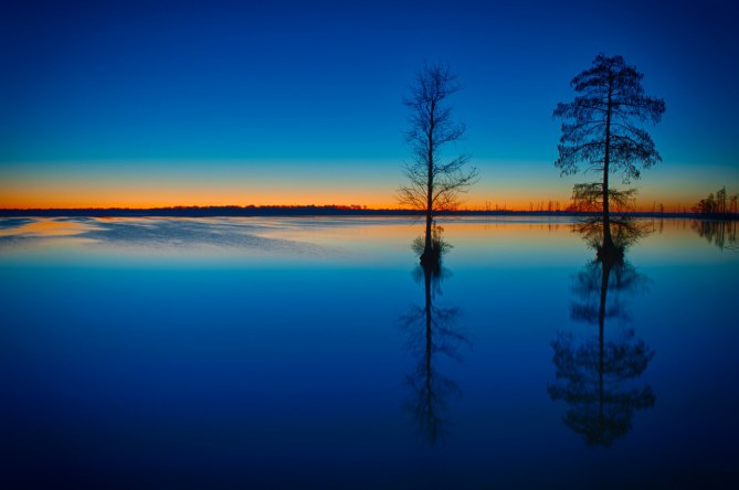 The Great Dismal Swamp National Wildlife Refuge is the largest intact remnant of a vast habitat that once covered more than one million acres of southeastern Virginia and northeastern North Carolina. The 112,000-acre Refuge is home to forests, marsh land and Lake Drummond – one of only two natural lakes in Virginia. Photo of Lake Drummond at twilight courtesy of Tom Hamilton. Posted on Tumblr by the US Department of the Interior, 6/22/15.