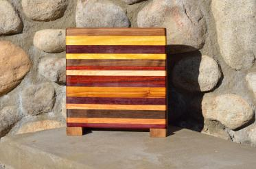 "Cheese Board # 15 - 035. Black Walnut, Yellowheart, Bloodwood, Padauk, Hard Maple, Purpleheart, Canarywood & Honey Locust. Edge grain. 9-1/2"" x 9-1/2"" x 3/4""."