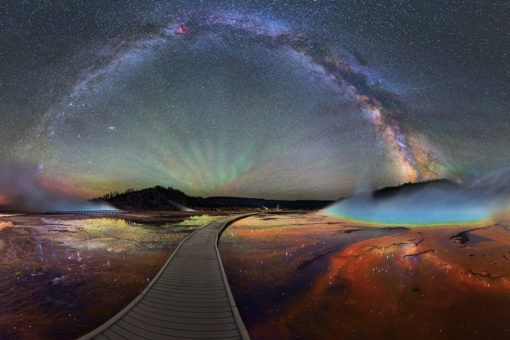 A trip to Yellowstone National Park isn't complete without seeing Midway Geyser Basin. A boardwalk leads you to the colorful Grand Prismatic Spring. At 370 feet in diameter and over 121 feet deep, Grand Prismatic is Yellowstone's largest hot spring. This jaw-dropping multi-image panorama shows Grand Prismatic Spring at night with the Milky Way sparkling above it and the stars reflected in the water below. Image courtesy of David Lane. Posted on the US Department of the Interior blog, 10/19/15.