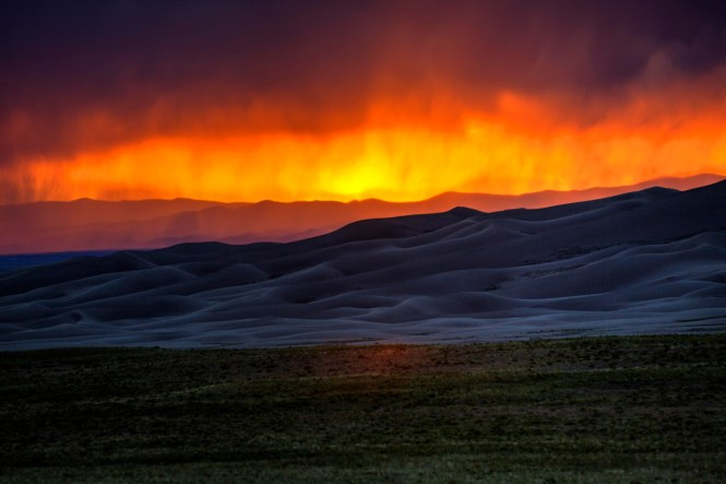 A fiery sunset overtakes the sky at Great Sand Dunes National Park and Preserve in Colorado, casting an otherworldly glow on the park's purple sands. Photo courtesy of Chris Wheeler. Posted on Tumblr by the US Department of the Interior, 2/9/16.