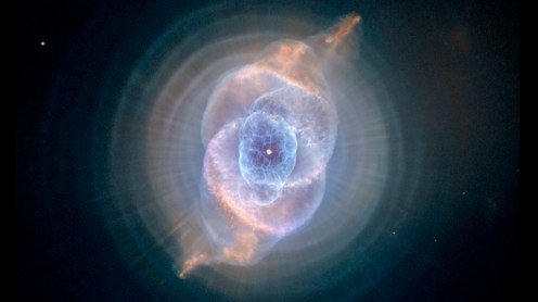 "Cat's Eye Nebula The Cat's Eye Nebula, one of the first planetary nebulae discovered, also has one of the most complex forms known to this kind of nebula. Eleven rings, or shells, of gas make up the Cat's Eye. Each ""ring"" is actually the edge of a spherical bubble seen projected onto the sky — that's why it appears bright along its outer edge. The view from Hubble is like seeing an onion cut in half, where each skin layer is discernible. Photo by Hubble Telescope."