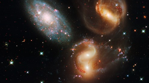 Stephan's Quintet A clash among members of a famous galaxy quintet reveals an assortment of stars across a wide color range, from young, blue stars to aging, red stars. Three of the galaxies have distorted shapes, elongated spiral arms, and long, gaseous tidal tails containing myriad star clusters, proof of their close encounters. Group member NGC 7320, at upper left, is actually a foreground galaxy about seven times closer to Earth than the rest of the group. Photo by the Hubble Telescope.
