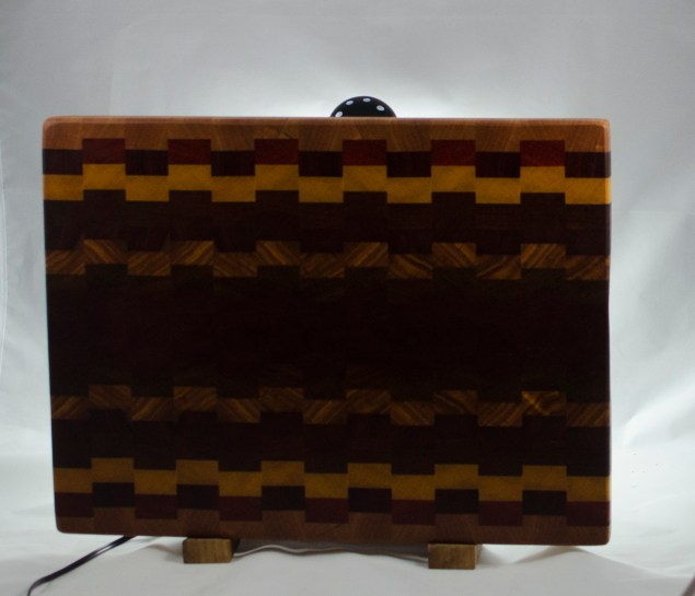"Cutting Board 16 - End 032. Cherry, Padauk, Yellowheart, Bubinga, Bloodwood, Canarywood & Purpleheart. End Grain. 14"" x 18"" x 1-1/4"". $225."