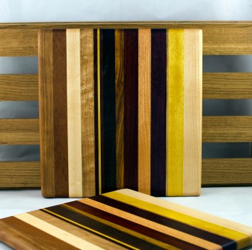 "Cheese Board 16 - 038. Jatoba, Cherry, Hard Maple, Yellowheart, Honey Locust, Padauk, Bloodwood & Black Walnut. 10"" x 10"" x 3/4""."