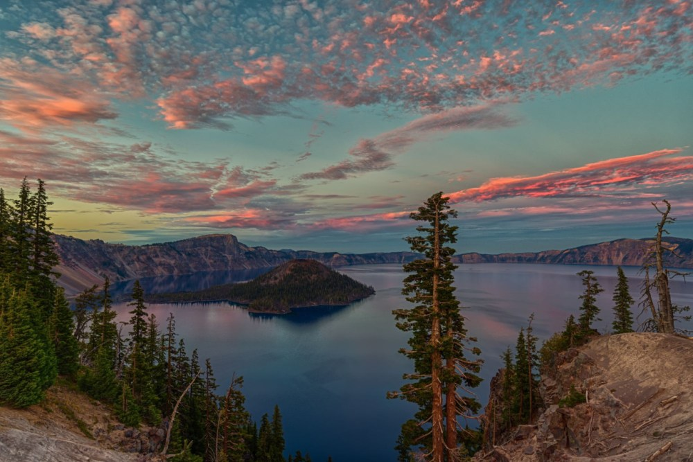 """With pinkish clouds over serene blue waters and stately trees, there's beauty everywhere you look at Crater Lake National Park in Oregon! Photographer Jeff C. Bryant waited until just the right moment to capture this striking sunset shot: """"As someone who photographs sunsets quite often, you win some and lose some. One thing I've learned is not to leave early!"""" Photo by Jeff C. Bryant, Posted on Tumblr by the US Department of the Interior, 9/10/16."""