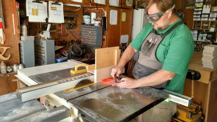 The featherboard keeps the blank up tight against the jig.
