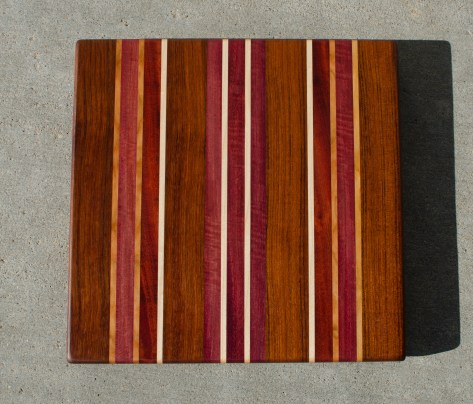 "Cutting Board 16 - Edge 029. Jatoba, Cherry, Bubinga, Bloodwood, Purpleheart & Hard Maple. Edge grain. 15"" x 15"" x 1-1/8""."